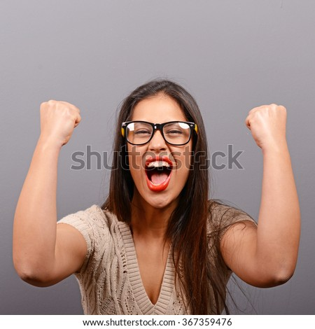 Portrait of happy woman exults pumping fists ecstatic celebrates success against gray background - stock photo