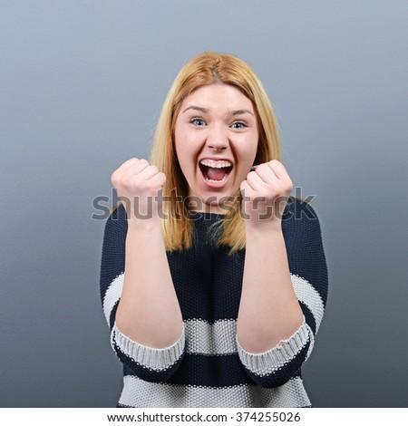 Portrait of happy woman exults pumping fists ecstatic celebrates success against gray background - stock photo