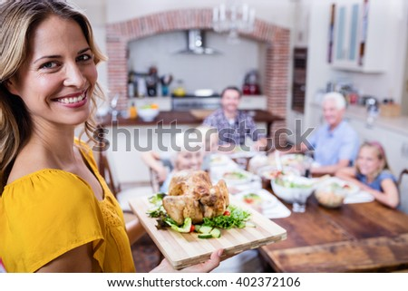 Portrait of happy woman holding a tray of roasted turkey and family dining in background - stock photo
