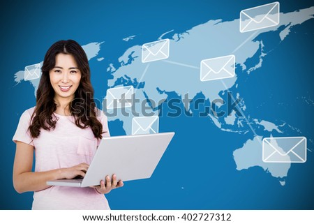 Portrait of happy woman holding laptop against map with emails