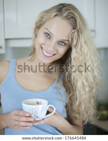 Portrait of happy woman holding tea cup in house