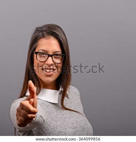 Portrait of happy woman holding thumbs up against gray background - stock photo