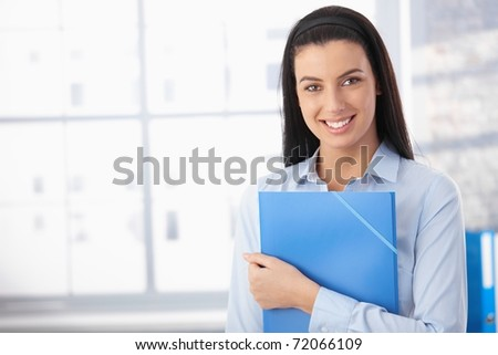 Portrait of happy woman in office, standing with folder, smiling at camera.? - stock photo
