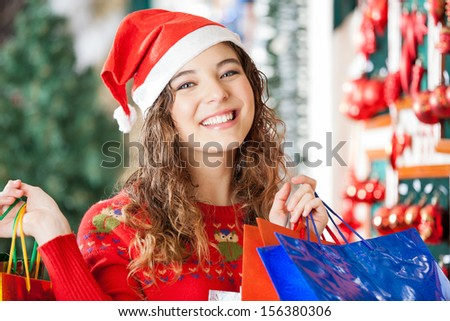 Portrait of happy woman in Santa hat carrying shopping bags at store - stock photo