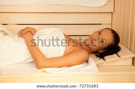 Portrait of happy woman lying in sauna, relaxing.? - stock photo