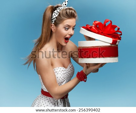 Portrait of happy woman opening gift box against blue background. Holidays, holiday, celebration, birthday and happiness concept  - stock photo