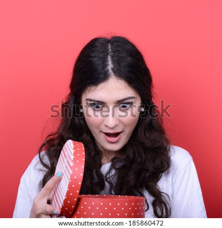 Portrait of happy woman opening gift box against red background - stock photo