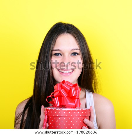 Portrait of happy woman opening gift box against yellow background - stock photo