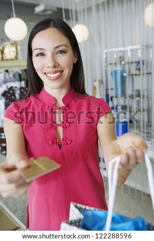 Portrait of happy woman paying with credit card in boutique - stock photo