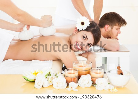 Portrait of happy woman receiving massage with herbal compress stamps on back at spa - stock photo