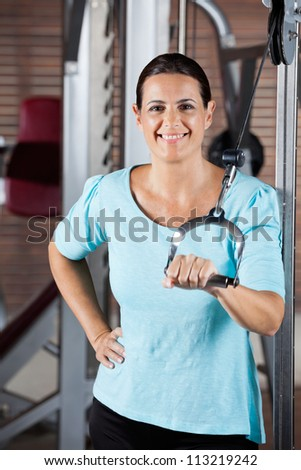 Portrait of happy woman training on machine in gym