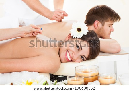 Portrait of happy woman undergoing acupuncture at beauty spa - stock photo