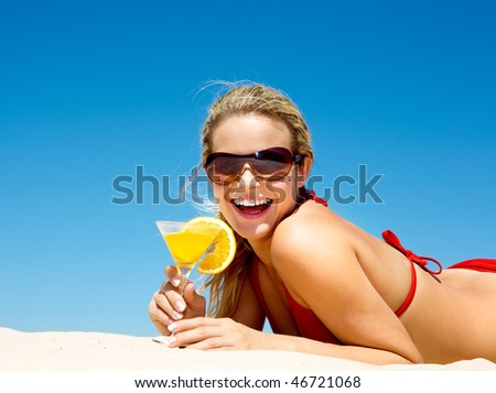 Portrait of happy woman wearing sunglasses holding cocktail at summer - stock photo