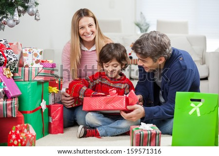 Portrait of happy woman with boy and man opening Christmas gift at home