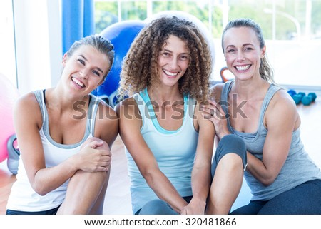 Portrait of happy women sitting in fitness studio