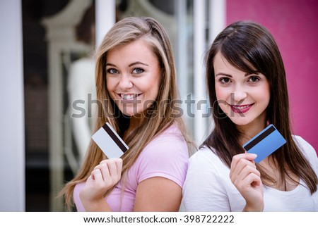 Portrait of happy women smiling and showing their credit cards while shopping in in mall