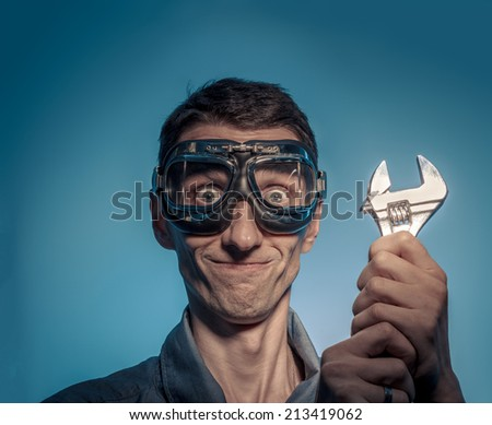 Portrait of happy worker in goggles with adjustable wrench. - stock photo