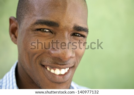 Portrait of happy young african american man looking at camera and smiling. Head and shoulders, copy space - stock photo