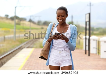 Portrait of happy young african woman at railroad station reading text message on mobile phone