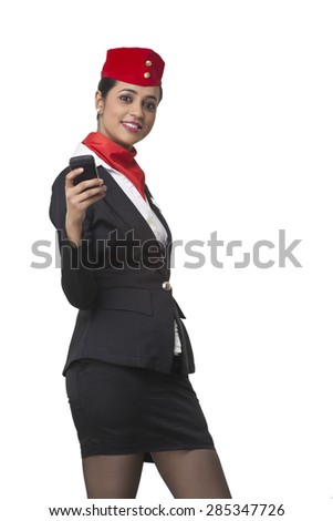 Portrait of happy young airhostess text messaging on cell phone isolated over white background