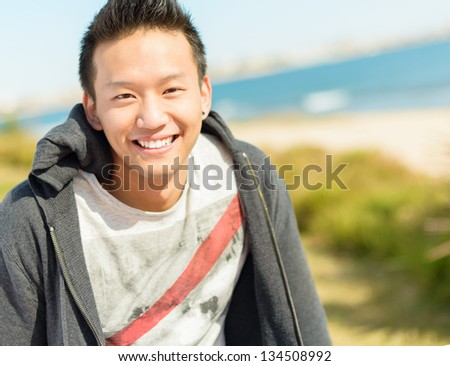 Portrait Of Happy Young Asian Man; Outdoors - stock photo