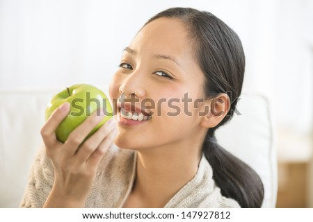 Portrait of happy young Asian woman eating granny smith apple on sofa