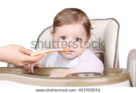 Portrait Of Happy Young Baby Boy eating mashed In High Chair - stock photo