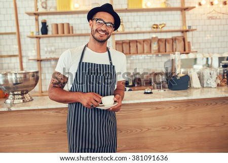 Portrait of happy young barista at work. Caucasian man wearing apron and hat standing in front of cafe counter with cup of coffee and looking at camera smiling. - stock photo