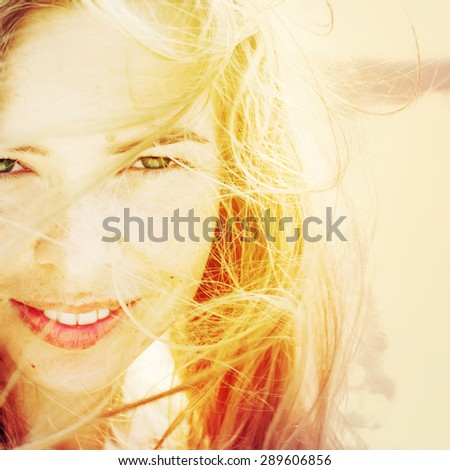 Portrait Of Happy Young Beautiful Woman with Hair Blowing in the Wind. in Sunlight. Warm Color Toned - stock photo