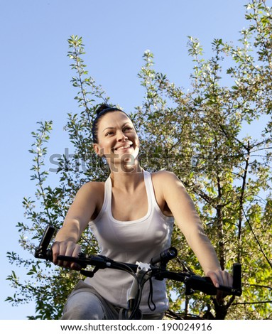 Portrait of happy young bicyclist riding in park - stock photo
