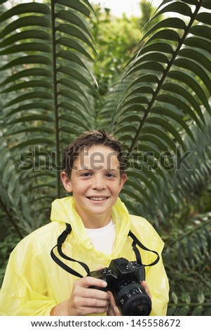 Portrait of happy young boy with camera by large fern in forest during field trip - stock photo