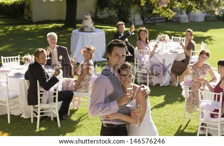 Portrait of happy young bride and groom embracing while wedding guests toasting champagne flutes in garden