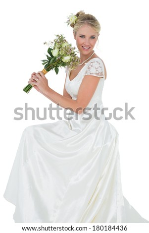 Portrait of happy young bride holding flower bouquet against white background