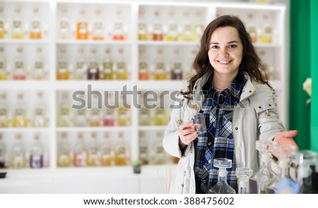 Portrait of happy young brunette shopping in perfume store  - stock photo