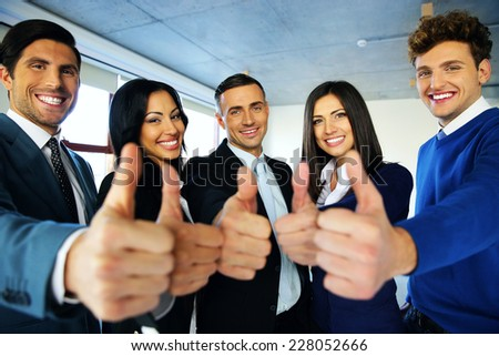 Portrait of happy young business people with thumbs up sign