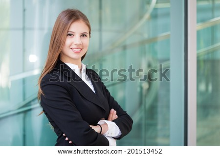 Portrait of happy young business woman in a modern environment - stock photo
