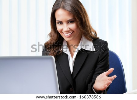 Portrait of happy young business woman working with laptop at office