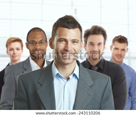 Portrait of happy young businessman and young businessteam at office. - stock photo