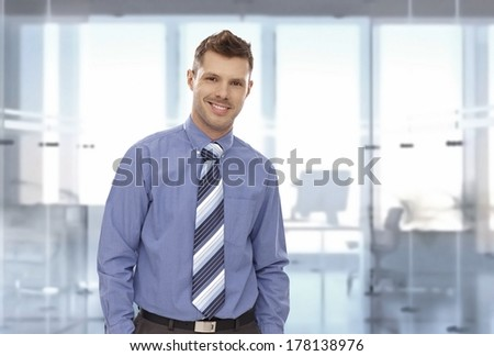 Portrait of happy young businessman at office, looking at camera, smiling. Copyspace. - stock photo