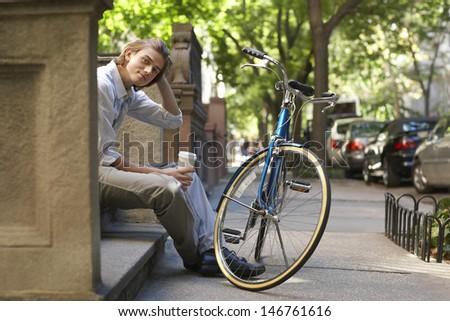 Portrait of happy young businessman holding disposable coffee cup while sitting on steps in front of bicycle - stock photo