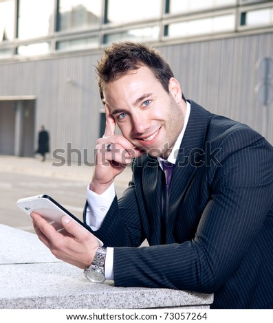 Portrait of happy young businessman holding touchscreen tablet - stock photo