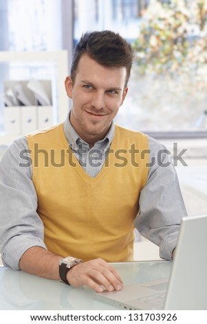 Portrait of happy young businessman sitting at desk working with laptop computer.