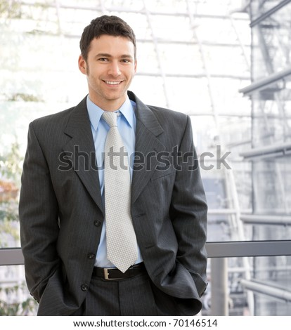 Portrait of happy young businessman standing on office corridor looking at camera, smiling.? - stock photo