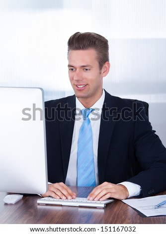 Portrait Of Happy Young Businessman Using Computer In Office