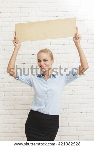 portrait of happy young businesswoman holding blank board - stock photo