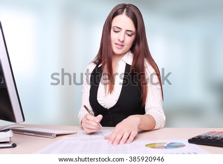 Portrait Of Happy Young Businesswoman Sitting At Desk Calculating Finance  - stock photo