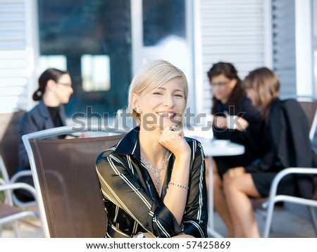 Portrait of happy young businesswoman sitting in chair outdoor, smiling. - stock photo