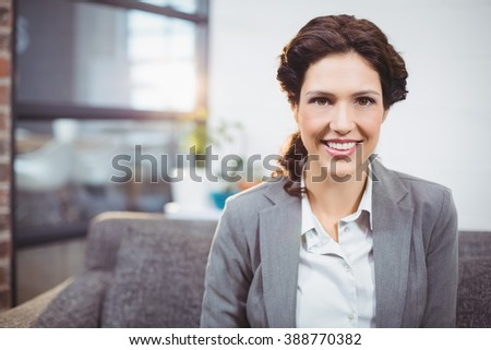 Portrait of happy young businesswoman sitting on sofa in office