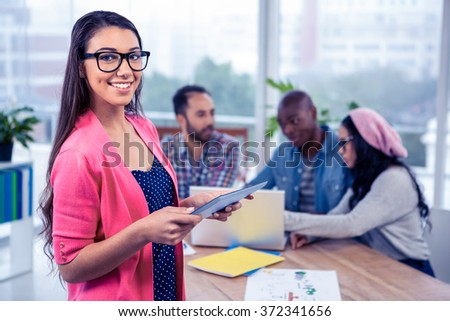 Portrait of happy young businesswoman using digital tablet while standing at office