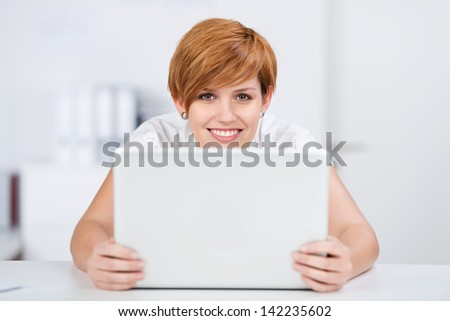 Portrait of happy young businesswoman with digital tablet at desk